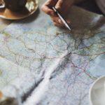 Stadtplan mit Kaffeetasse und einer Hand mit Kugelschreiber
