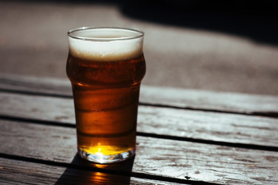 Glas Bier in der Sonne auf einem Holzbrett
