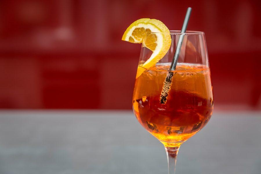 Ein Glas Aperol Spritz mit Orange und Strohhalm