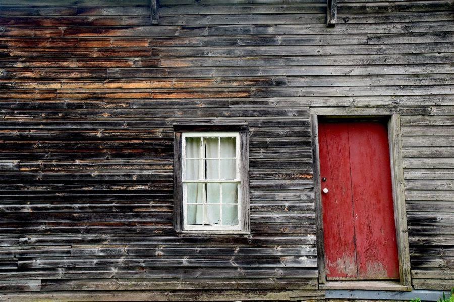 Berghütte mit roter Tür und Fenster mit Vorhang