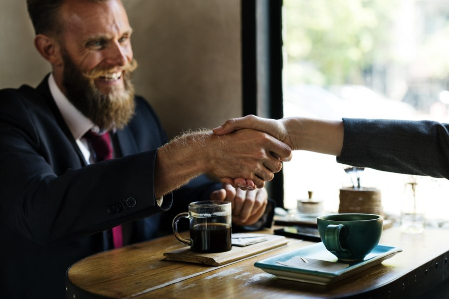 Mann schüttelt in die Hand einer Frau in einem Kaffeehaus