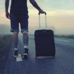 Mann mit Koffer auf der Straße Packliste für Salzburg