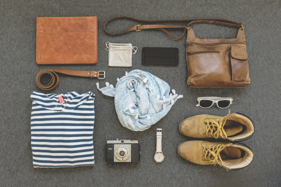 Flatlay von Tasche, Kleidung, Schuhe und Sonnenbrille