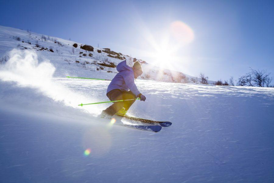 Skifahrer mit blauer Jacke fährt eine Piste hinab