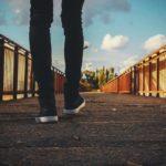 Füße von einem Menschen der über eine Brücke geht