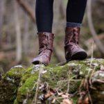 Frau in Wanderschuhen steht auf einem mit Moos bewachsenen Felsen