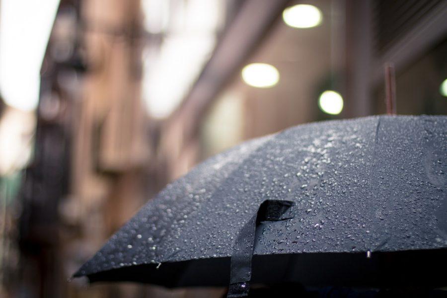 Regenschirm mit unscharfer Häuserfront im Hintergrund
