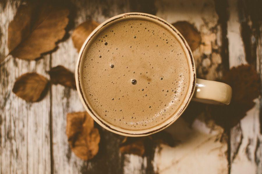 Kaffee mit Crema auf einem Holzbrett mit Laub