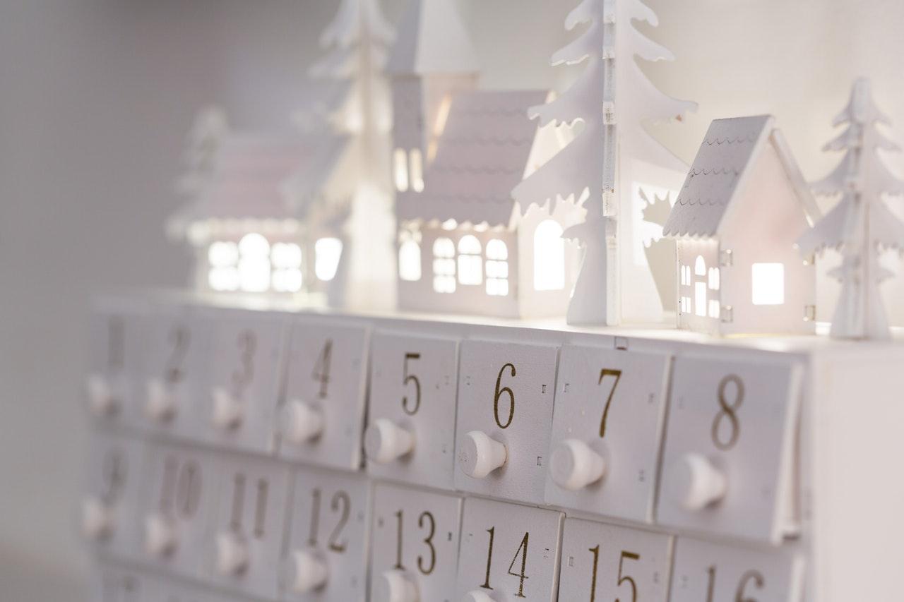 Weißer Adventskalender mit beleuchteten Häuschen darauf