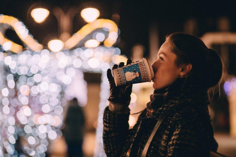Frau trinkt Heißgetränk inmitten weihnachtlicher Beleuchtung