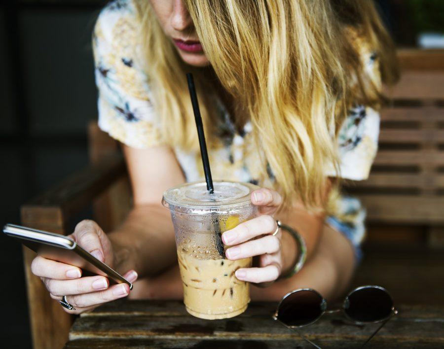 Frau sucht etwas am Handy und trinkt Kaffee