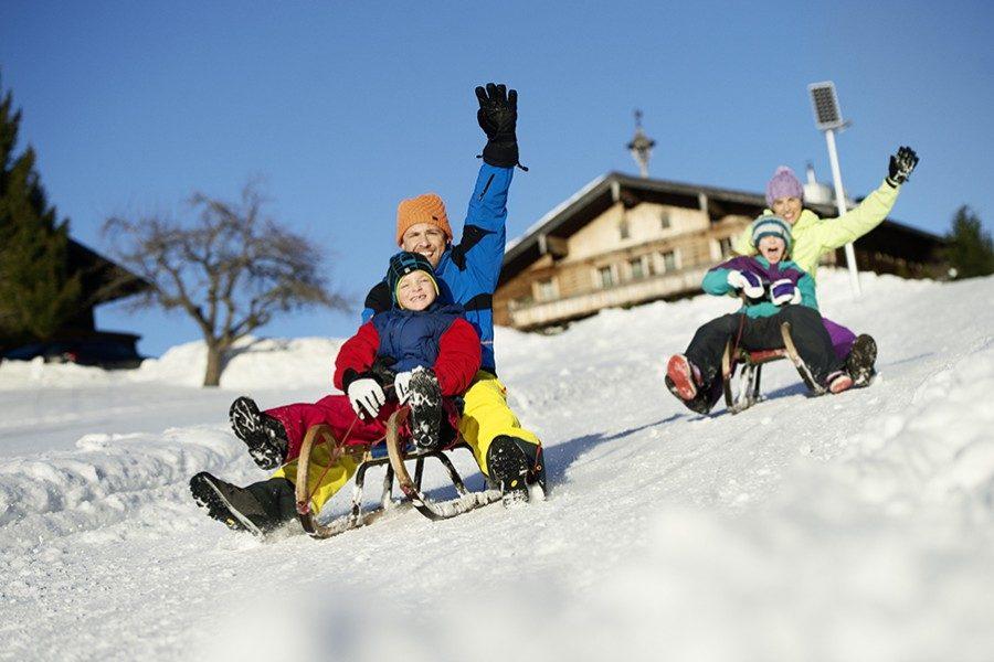 Familie fährt auf Schlitten Berg hinunter