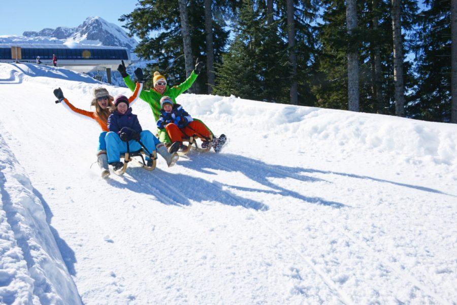 Familie fährt Rodelbahn hinunter