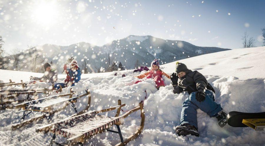 Kinder spielen mit Rodeln im Schnee